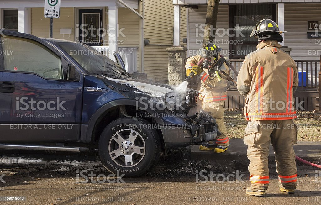 Firefighters puting out car fire royalty-free stock photo