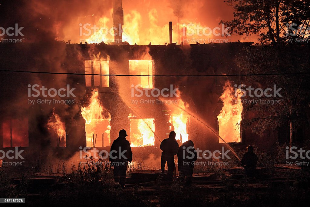 firefighters silhouettes on fire background stock photo