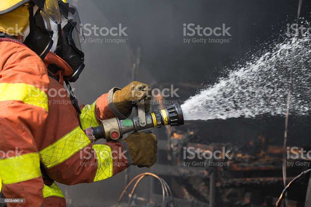 2 firefighters spraying water in fire fighting operation stock photo
