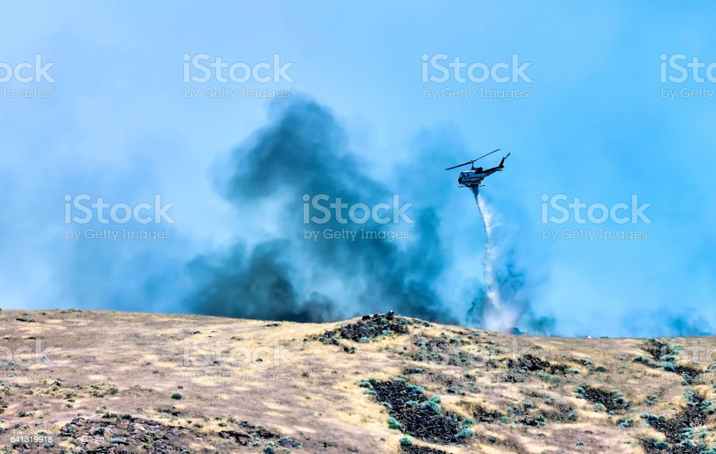 Firefighting helicopter dropping water on a desert wildfire stock photo