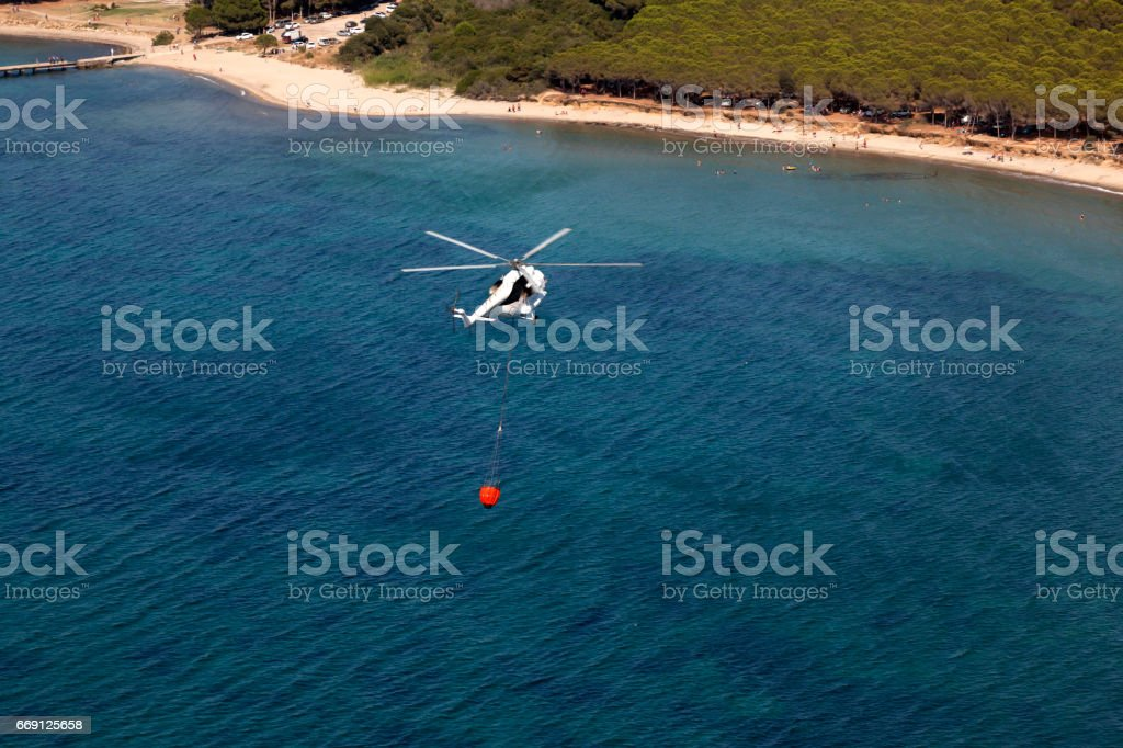 Firefighting Helicopter with Water Bucket on Sea stock photo