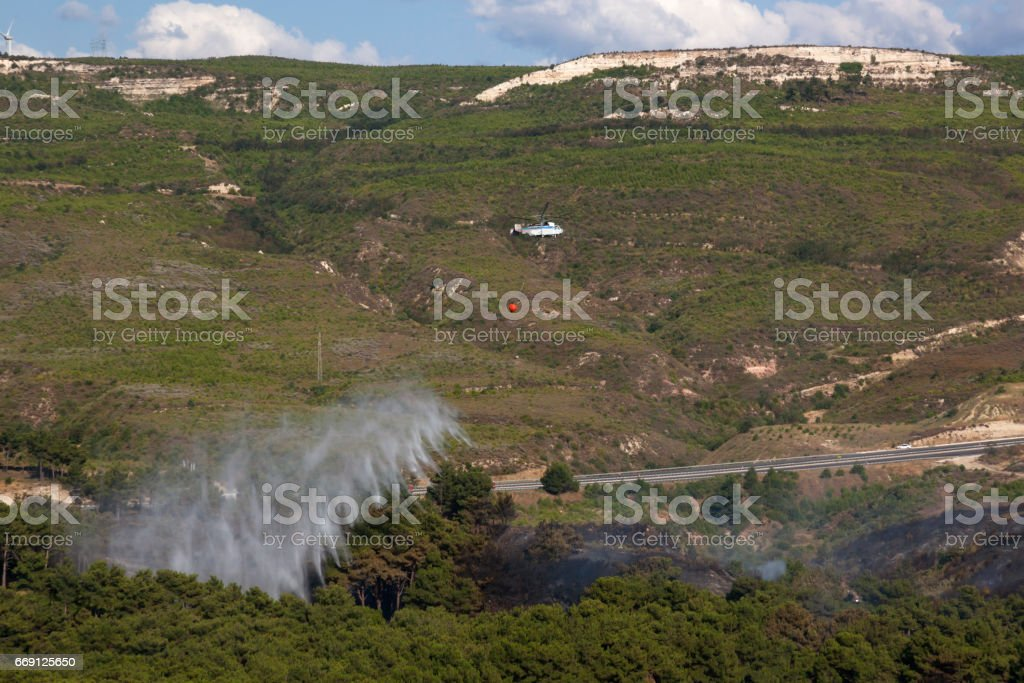 Firefighting Helicopter Working with Water Bucket stock photo