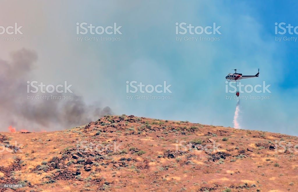 Firefighting water tanker helicopter dropping water on a desert wildfire. stock photo