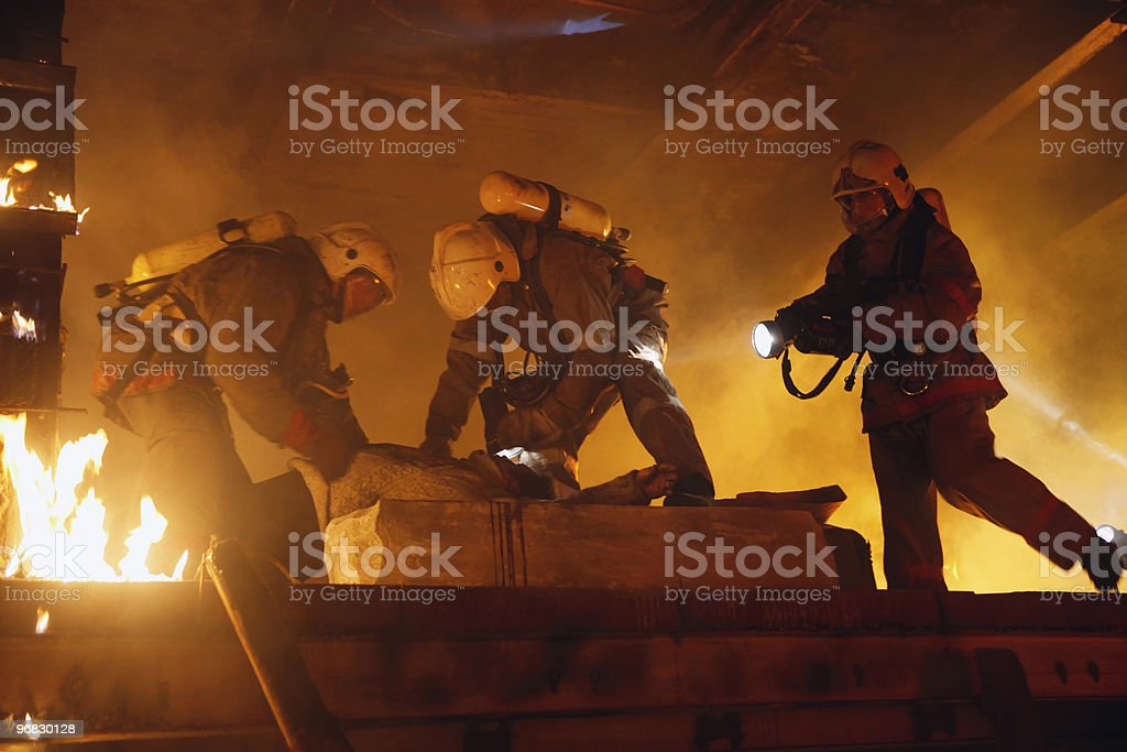 Firefights rescuing an accident victim in a burning house  royalty-free stock photo