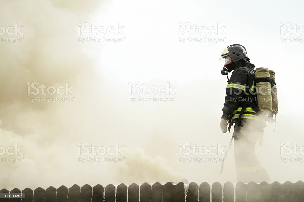 Fireman immersed in smoke while on the job stock photo