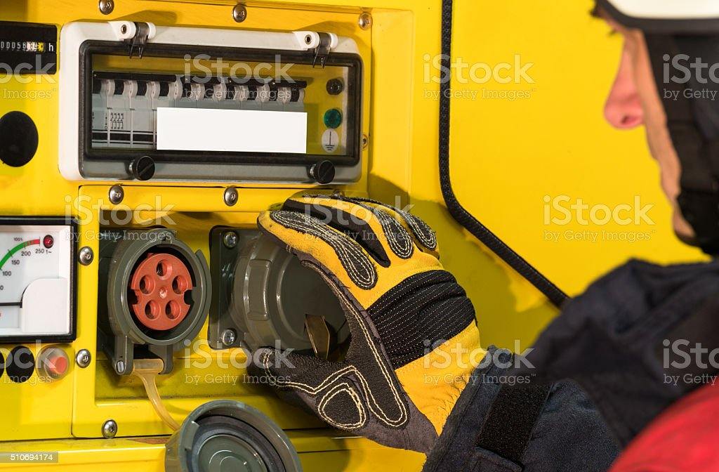 Fireman in action at the power generator stock photo