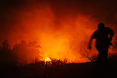 Fireman runs towards raging bush fire