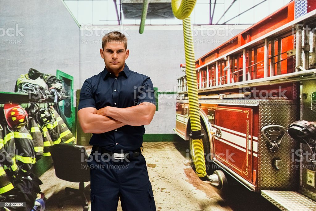 Fireman standing in fire station stock photo
