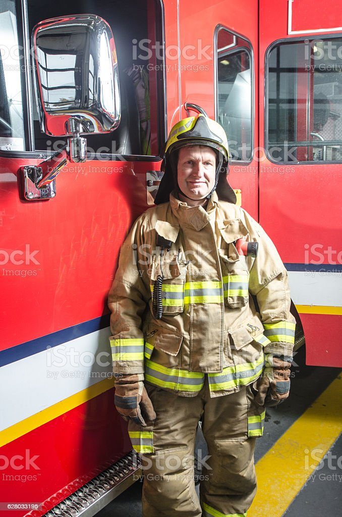 Fireman wearing full protection suits besides his truck stock photo