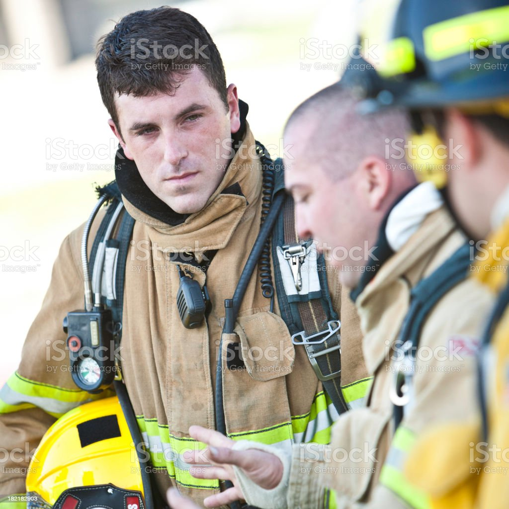 Fireman with Gear On Listening to Fellow Firefighter Talking stock photo