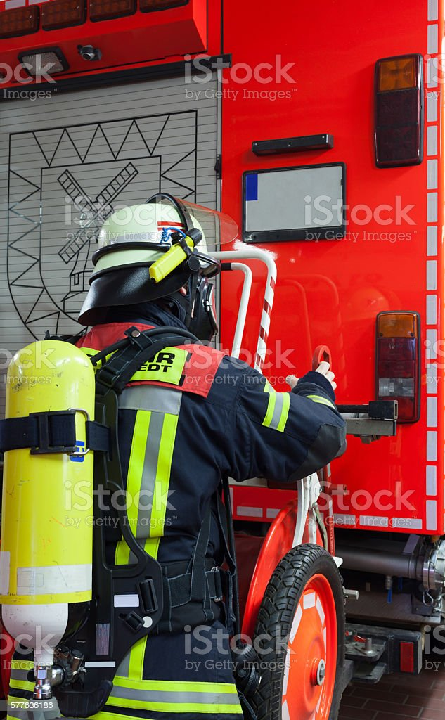 Fireman with oxygen bottle with mask on emergency vehicle stock photo