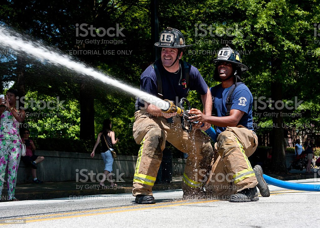 Firemen Aim Hose At Target In Atlanta Muster Competition stock photo