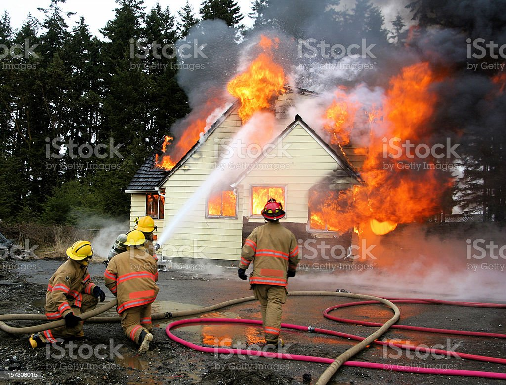 Firemen  Fighting Residence House Fire stock photo