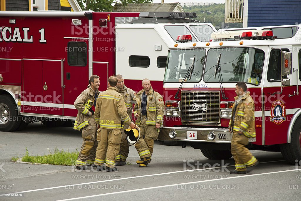 Firemen in Front of Their Trucks stock photo