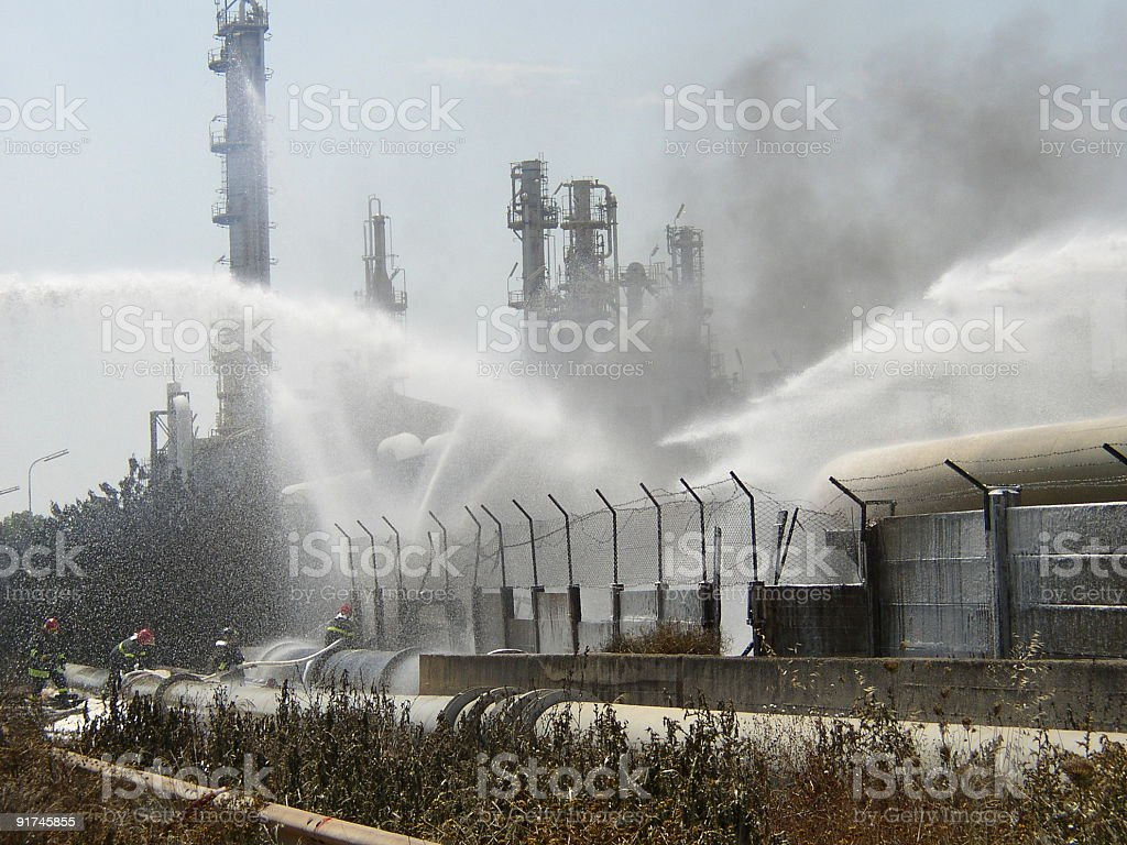 Firemen putting out a fire with hoses of water at refinery stock photo