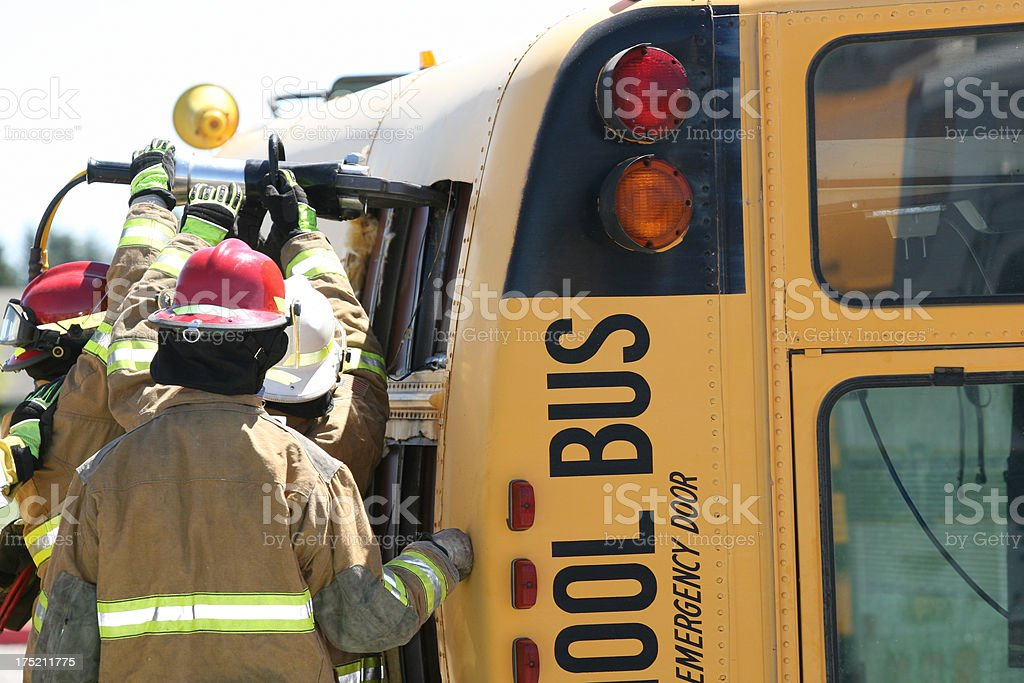 Firemen rescuing students from wrecked school bus royalty-free stock photo