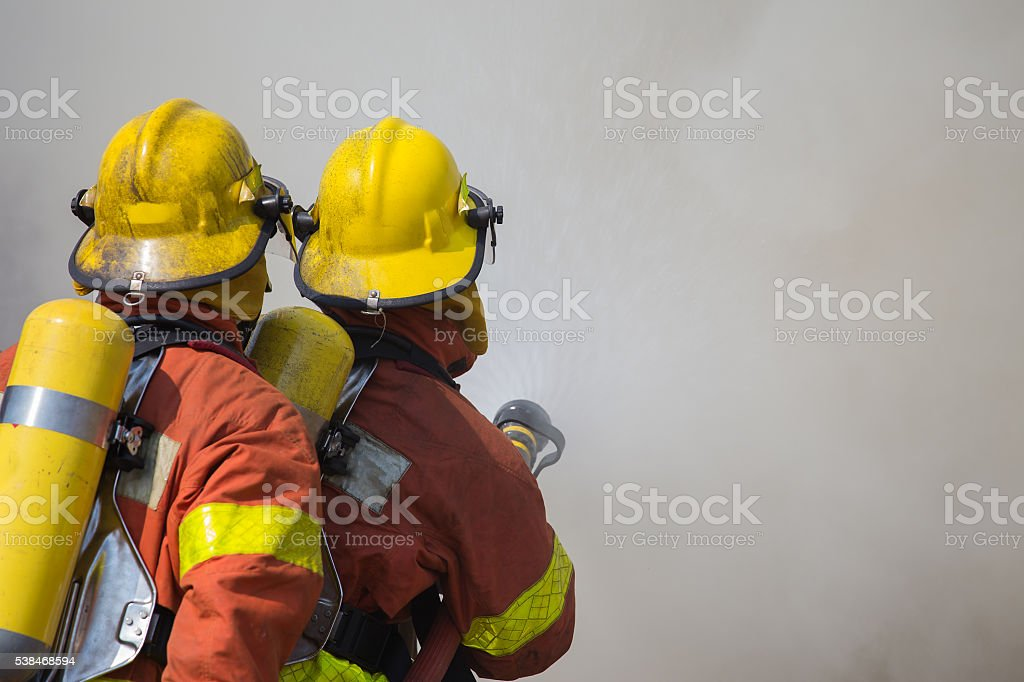 2 firemen spraying water in fire and smoke stock photo