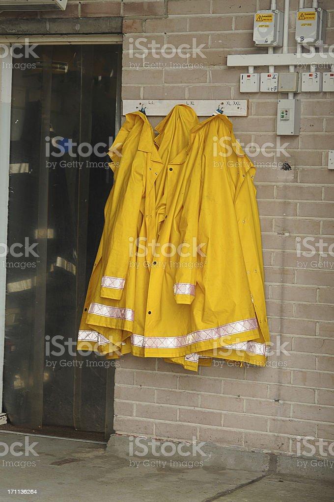Firemen's yellow waterproofs hanging on wall stock photo