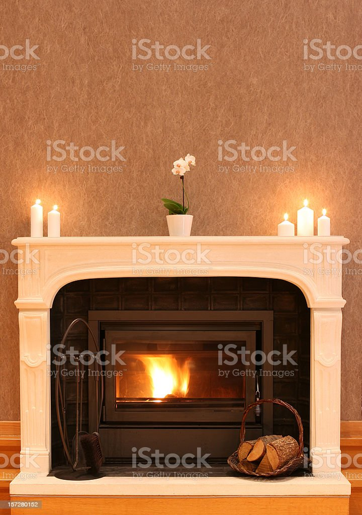 Fireplace with burning fire and empty wall stock photo