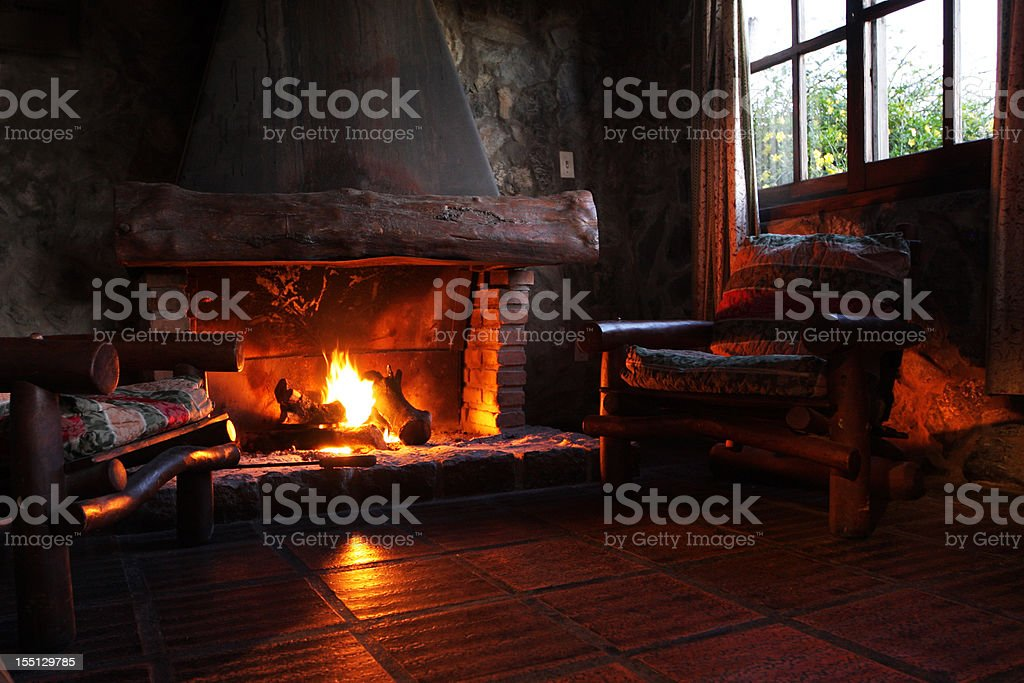 Fireplace with wooden logs, chairs and window stock photo