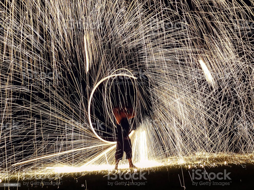 Firestarter performing amazing fire show with sparkles stock photo