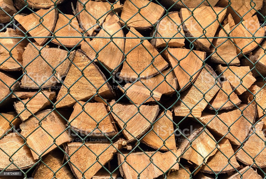 Firewood behind a green grid royalty-free stock photo