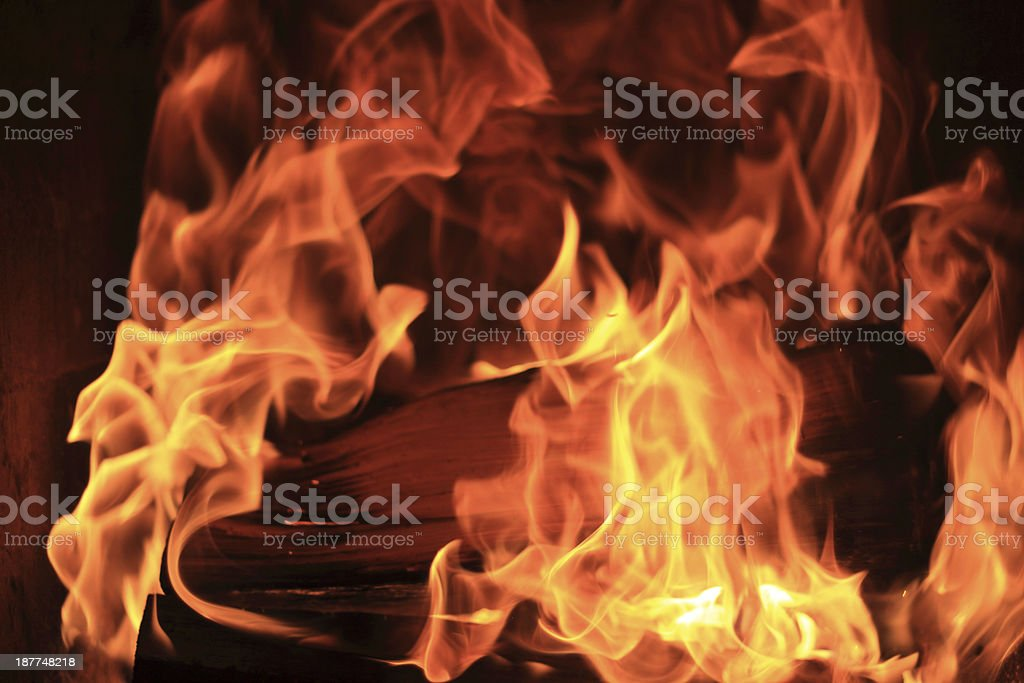 firewood in a fireplace producing whirling flames stock photo