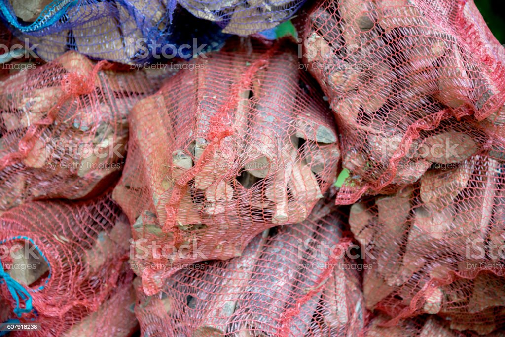 Firewood in net bag sold in the store stock photo