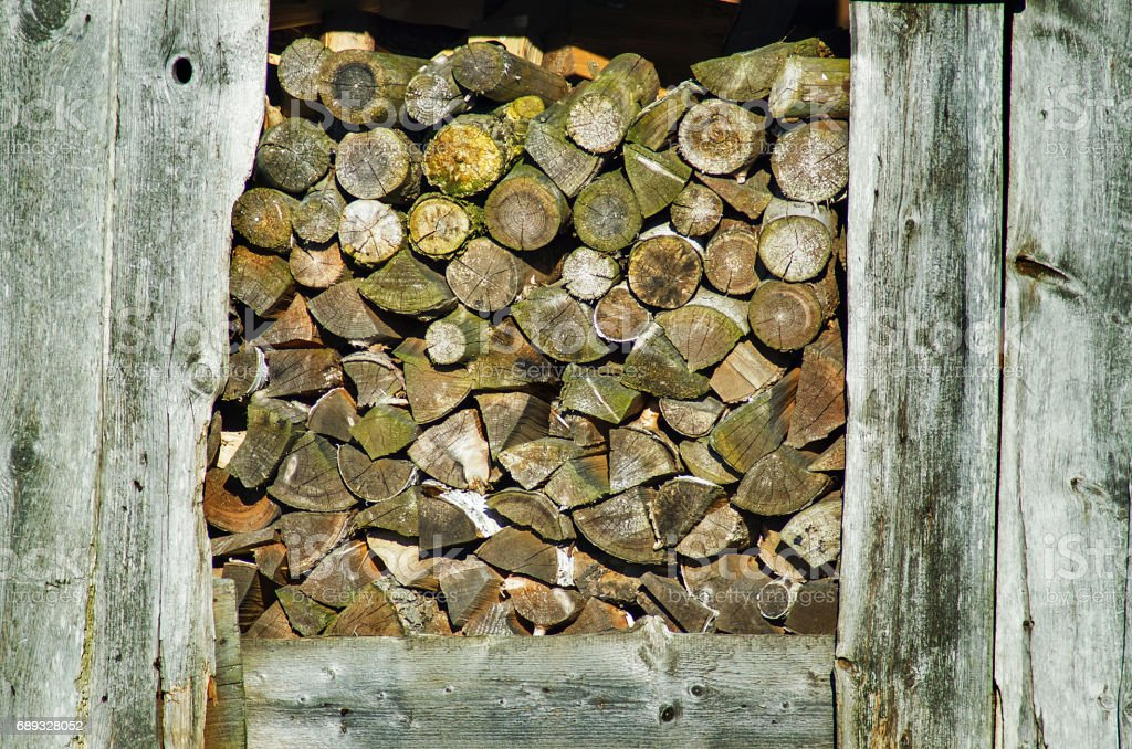 Firewood in the old woodshed, a wood reserve in the village stock photo