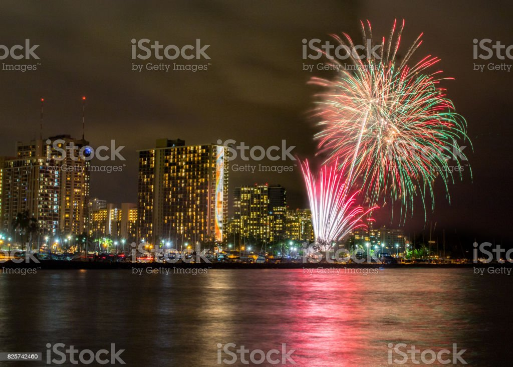 Fireworks at harbor with reflection in water at Magic Island, Honolulu stock photo