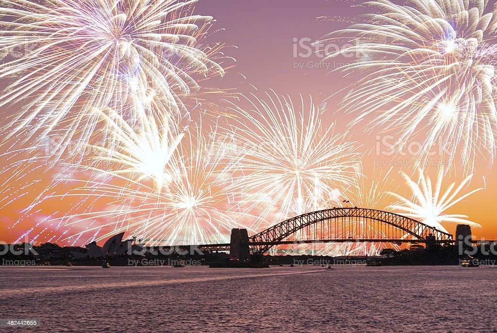 Fireworks behind Sydney Harbour Bridge at dusk stock photo