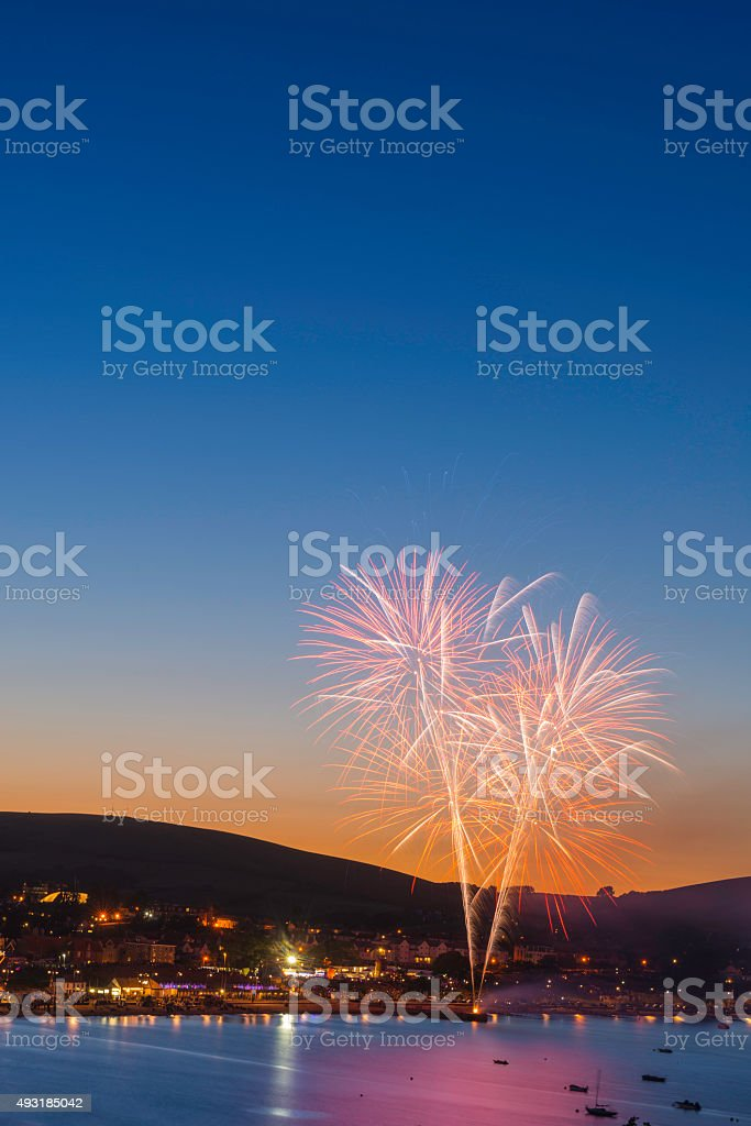 Fireworks exploding colorfully above harbor town into clear blue sky stock photo