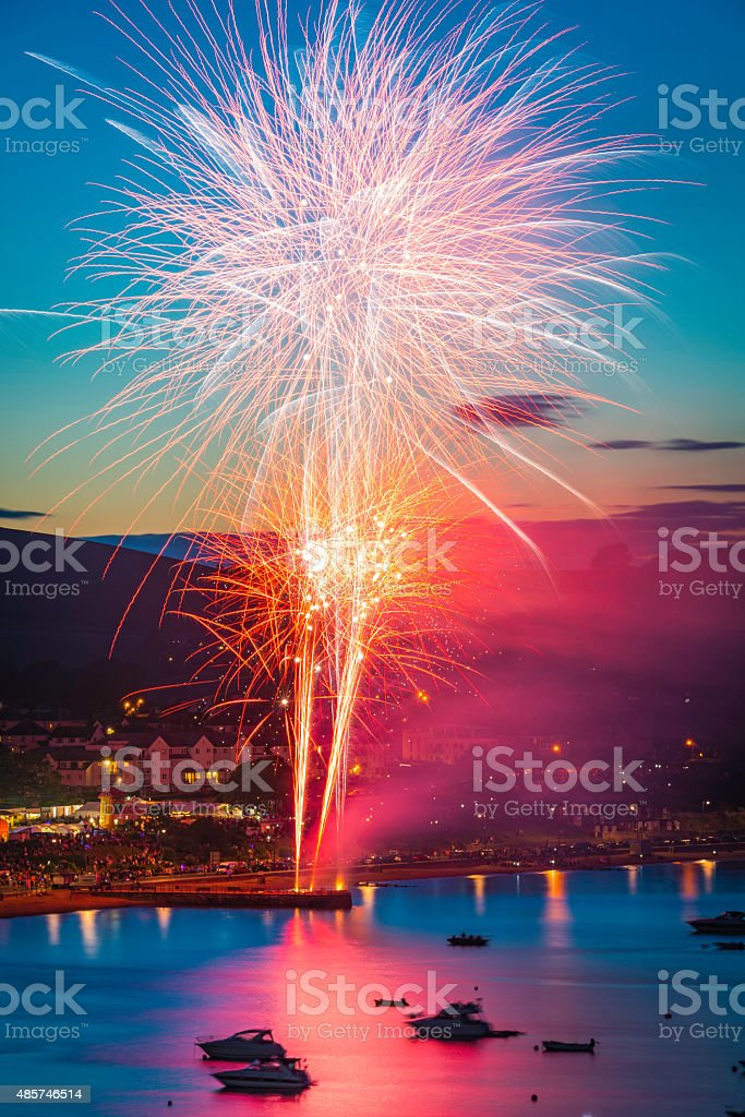 Fireworks exploding colourfully above seaside harbour resort Swanage Dorset stock photo
