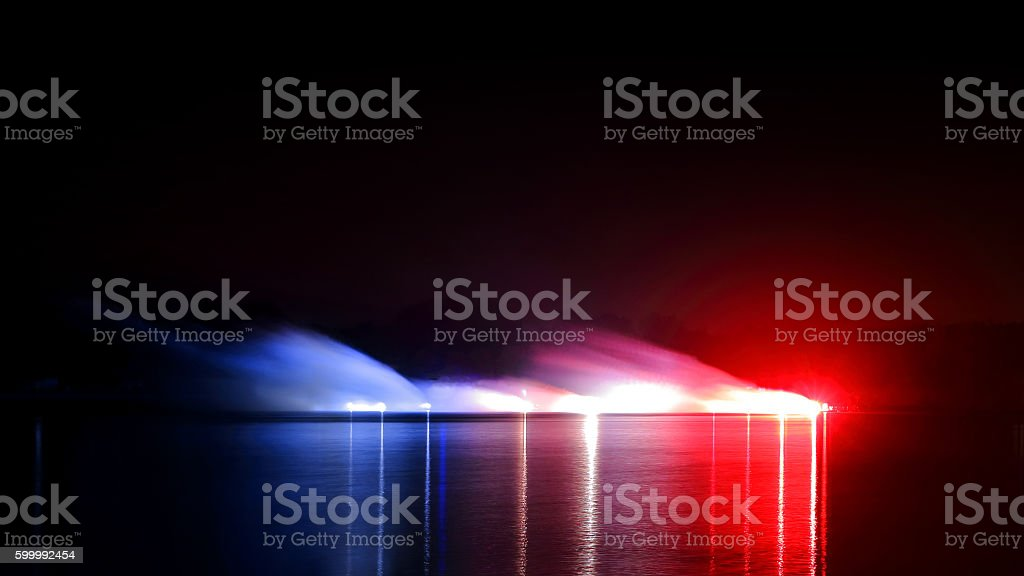 Fireworks pyrotechnic fumes red white and blue with water reflections stock photo