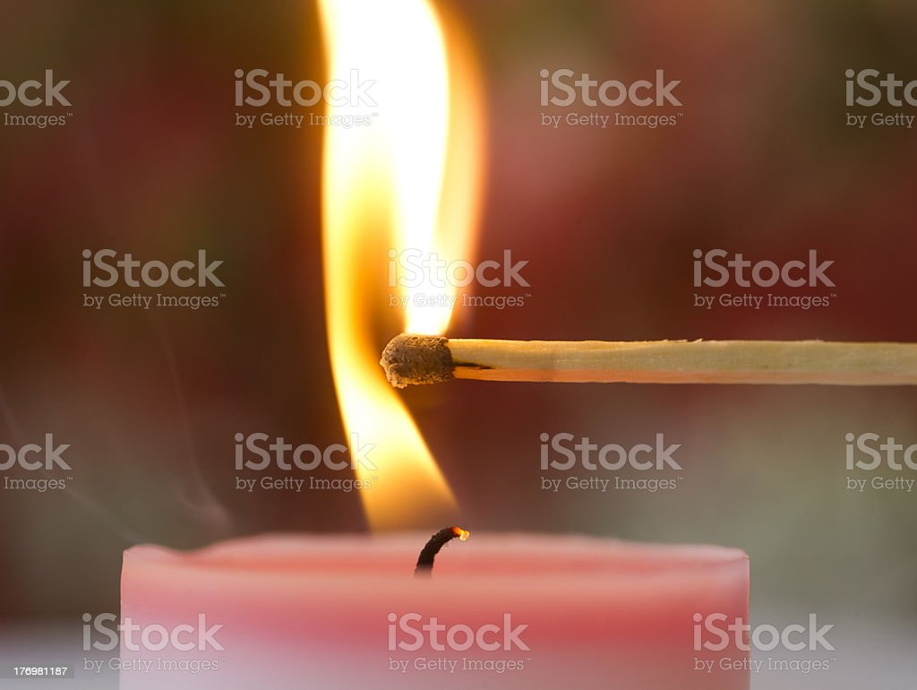 Firing a candle with match stock photo
