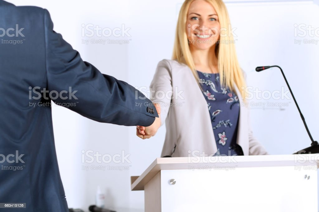 A firm handshake between beautiful businesswoman and man  at the presentation stock photo