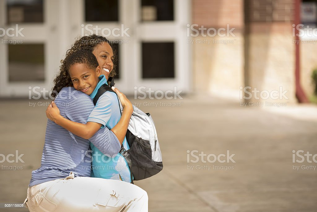 First day of school.  Little boy hugs mom goodbye. stock photo
