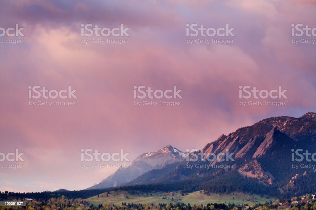 First light peeking over top of Boulder Colorado Flatirons stock photo