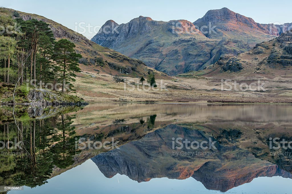 First Light Shining On Mountain Peaks With Reflections. stock photo