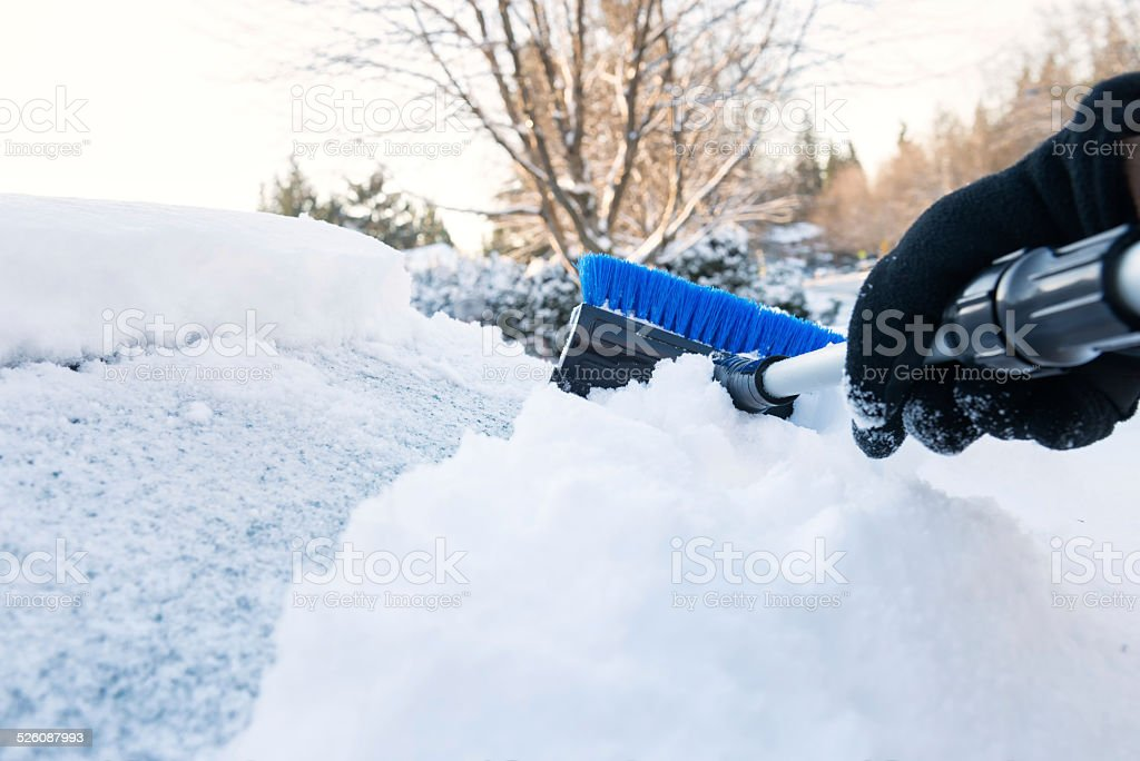 First Person Perspective, Hand Clearing Snow Off Car with Scraper stock photo