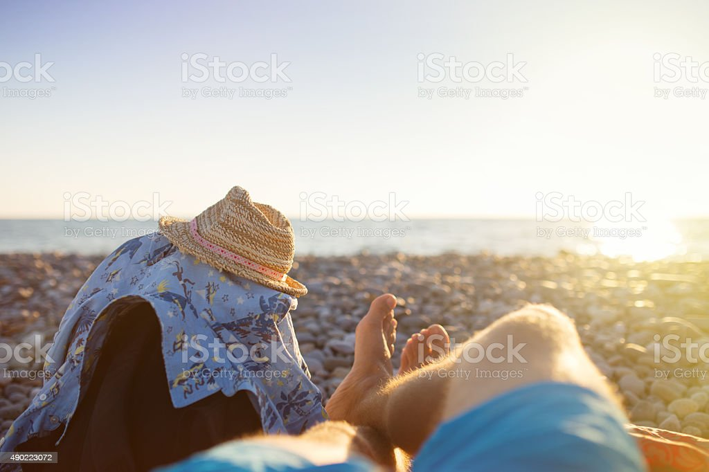 First person perspective of man legs on sunset beach. stock photo