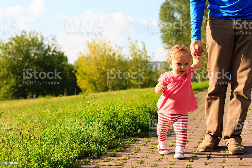 first steps of little girl with dad in the park stock photo