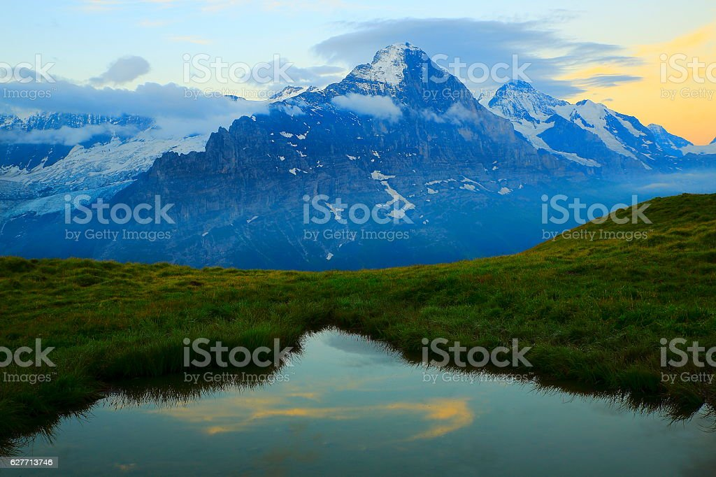 First Swiss Alps: Eiger, mirrored lake above Grindelwald, dramatic sunrise stock photo