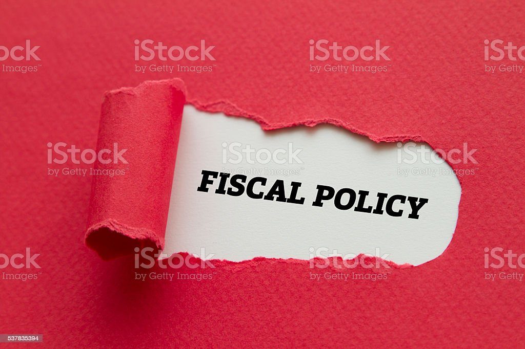 Fiscal Policy written under torn paper. stock photo
