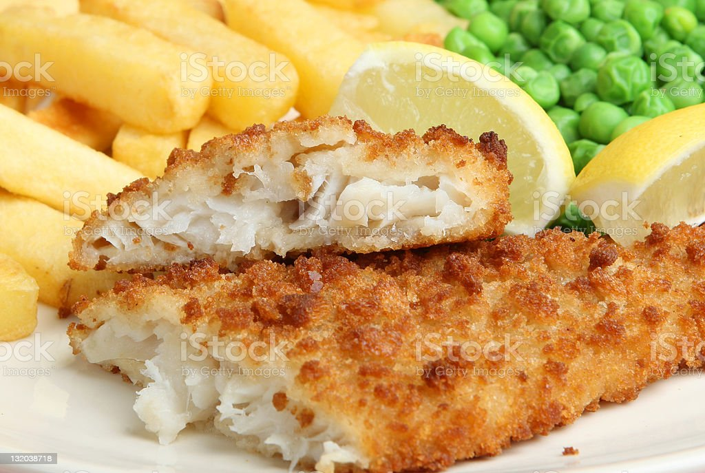 Fish and chips with lemon and petit pois stock photo