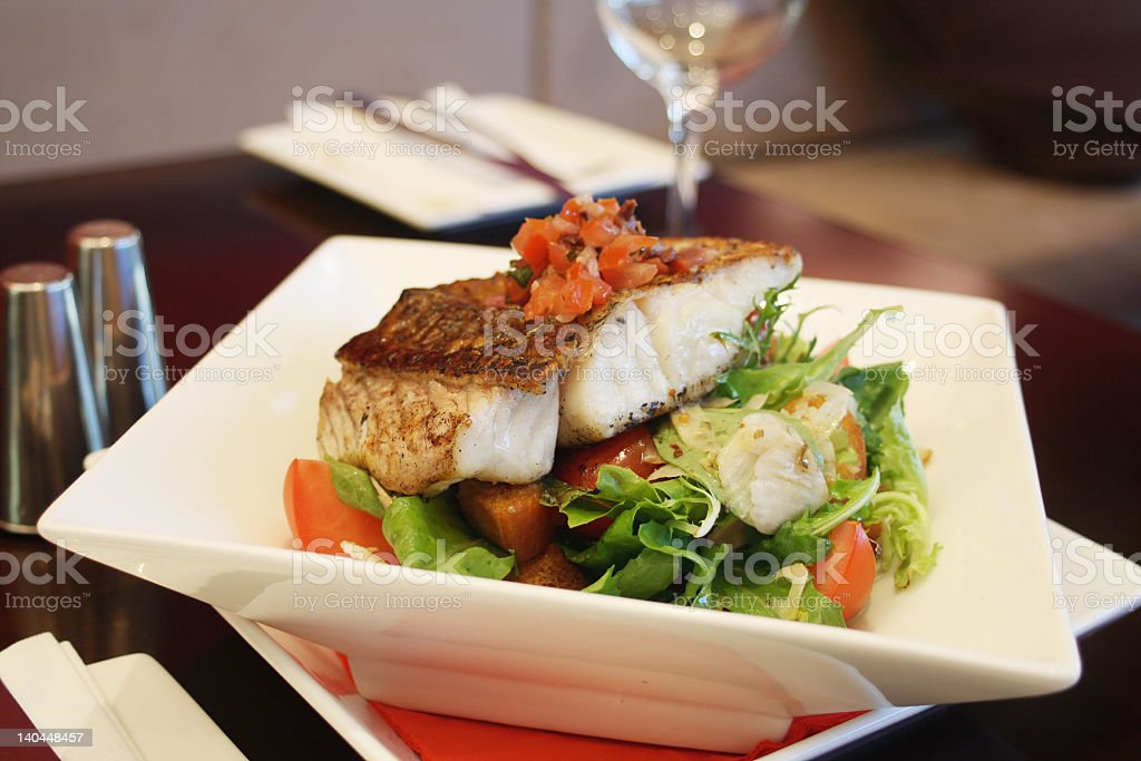A fish and salad dinner in a white bowl stock photo