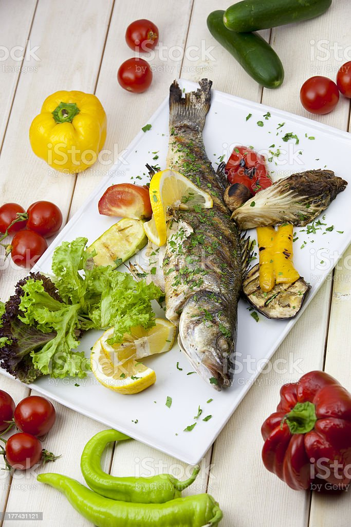 fish and vegatables on the wooden table stock photo
