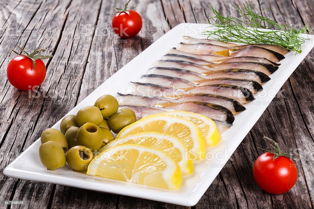 fish appetizer  with sliced lemon, green olives and tomatoes stock photo