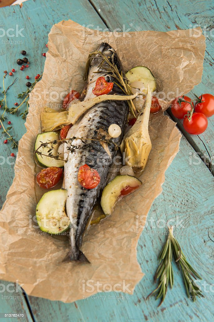 Fish baked in paper with vegetables on vintage wooden table stock photo