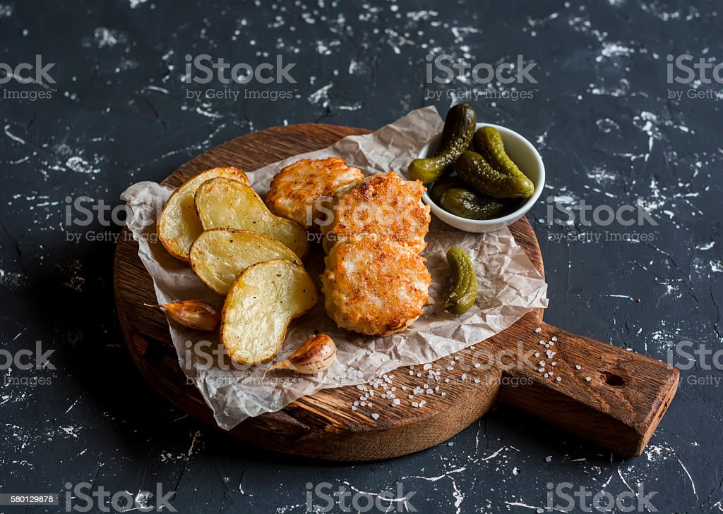 Fish balls and baked potatoes on wooden cutting board stock photo